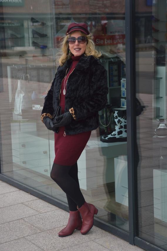Bordeauxrotes Strickkleid mit schwarzer Fellimitat-Jacke kombiniert
