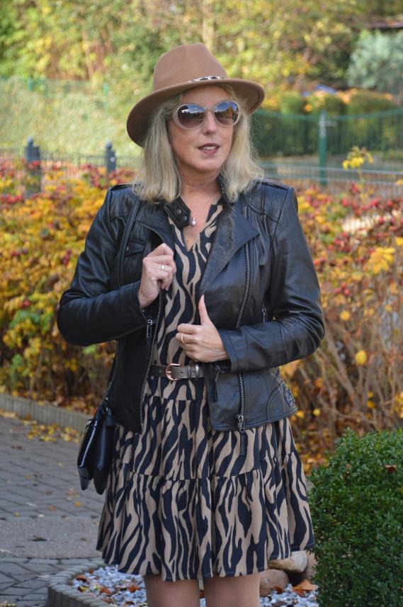 Zebra-Kleid mit schwarzer Lederjacke kombiniert